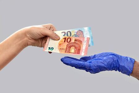 close up of hand in medical glove giving money Reklamní fotografie
