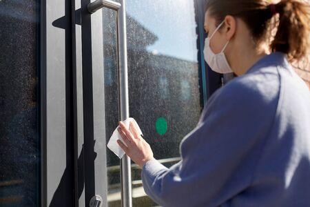 woman in mask cleaning door handle with wet wipe Foto de archivo