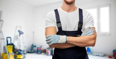 close up of male builder in overall and gloves