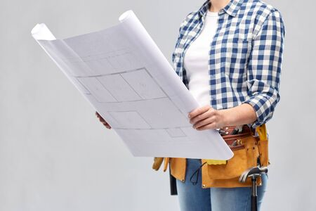 Female builder with blueprint and working tools