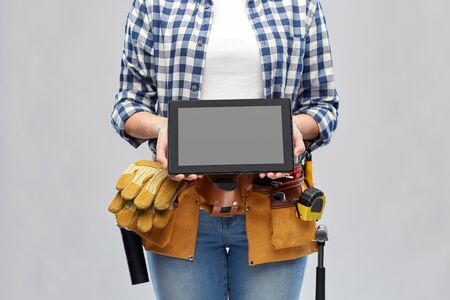 Woman builder with working tools showing tablet pc
