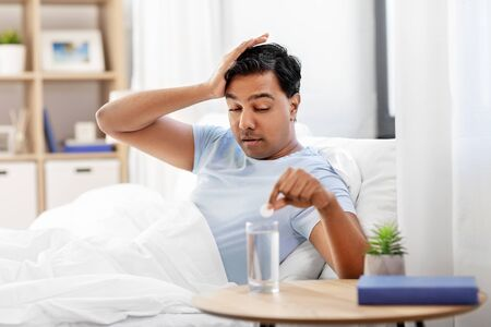 sick man in bed with medicine and glass of water