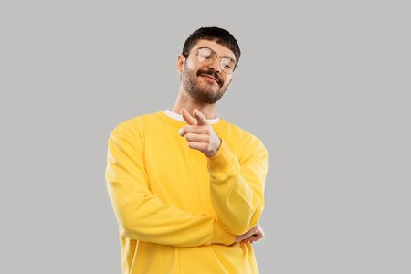 man in yellow sweatshirt pointing finger to camera