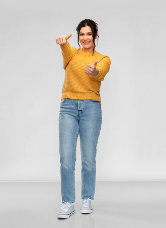 happy smiling young woman showing thumbs up