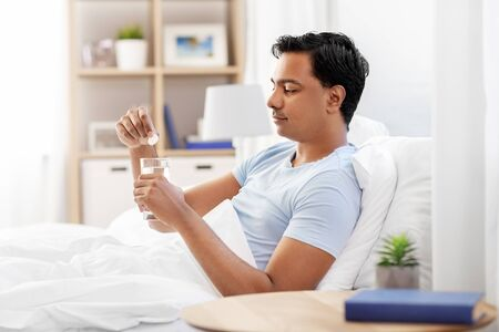 man in bed dropping medicine into glass of water