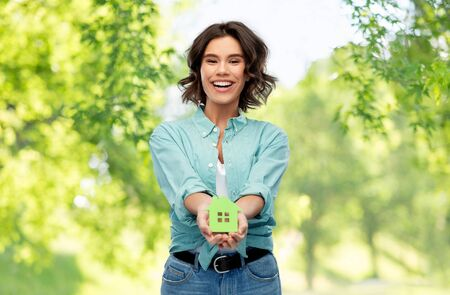 Smiling young woman holding green house Stock Photo