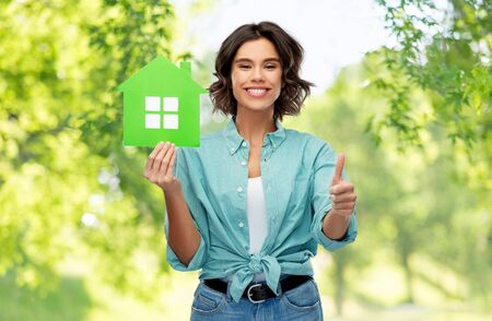 smiling woman with green house showing thumbs up Stock Photo