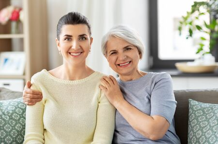 senior mother with adult daughter hugging at home