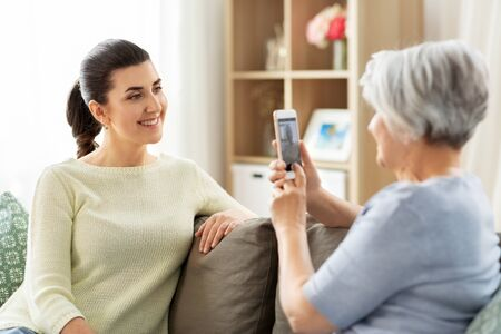 senior mother photographing adult daughter at home