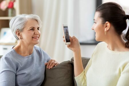 adult daughter photographing senior mother at home