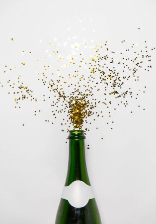 champagne bottle and golden glitters on white
