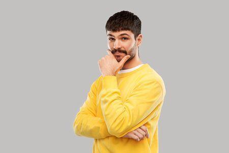 thinking young man in yellow sweatshirt