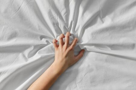 hand of woman squeezing white bed sheet Imagens