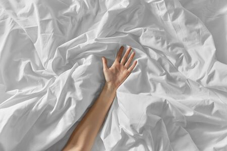 hand of woman lying on rumpled bed sheet