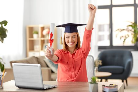 e-learning, education and people concept - happy smiling female graduate student in mortarboard with laptop computer and diploma celebrating success at home