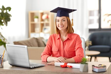 e-learning, education and people concept - happy smiling female graduate student in mortarboard with laptop computer and diploma at home Standard-Bild