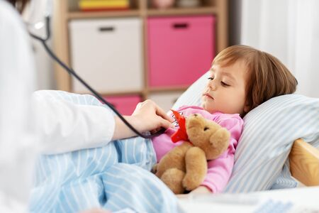 healthcare, medicine and people concept - doctor with stethoscope checking sick little girl's lungs at home Imagens