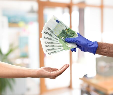 finance, payment and pandemic concept - close up of one hand in medical glove giving money to another over office background