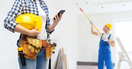 woman or builder with phone and working tools