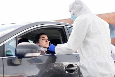 healthcare worker making coronavirus test at car Foto de archivo