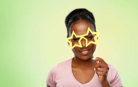 party props, photo booth and people concept - happy african american young woman with star shaped glasses over lime green natural background