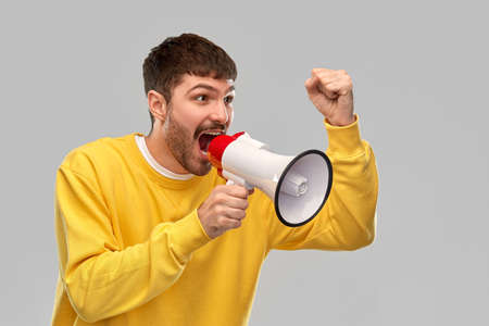 communication and people concept - angry young man in yellow sweatshirt shouting to megaphone over grey background