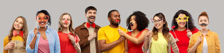 photo booth and fun concept - happy smiling people with party props over grey background