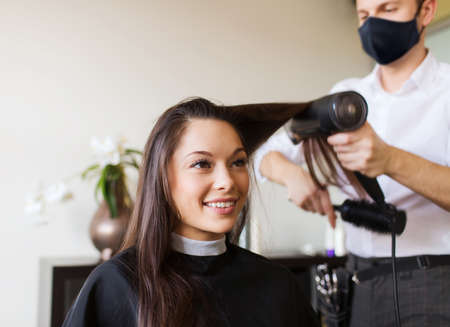 beauty, hairdressing and health safety concept - young woman wearing face protective medical mask for protection from virus disease and hairdresser with fan making hot styling at hair salon