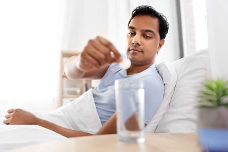 people, bedtime and rest concept - indian man lying in bed and dropping medicine pill into glass of water at home Фото со стока