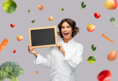 happy female chef holding chalkboard over food
