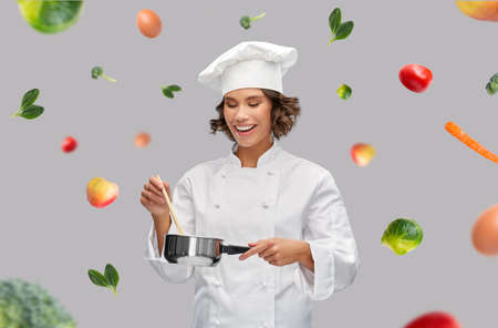 happy smiling female chef with saucepan over food Stock Photo