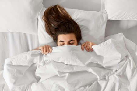 woman lying in bed under white blanket or duvet