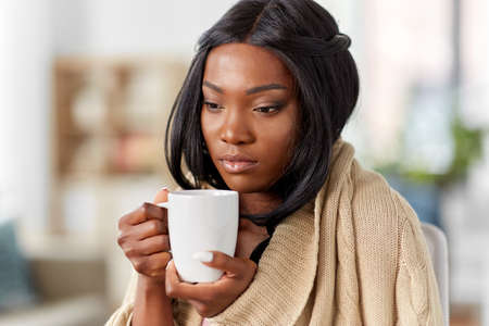 sick african amercian woman drinking tea at home