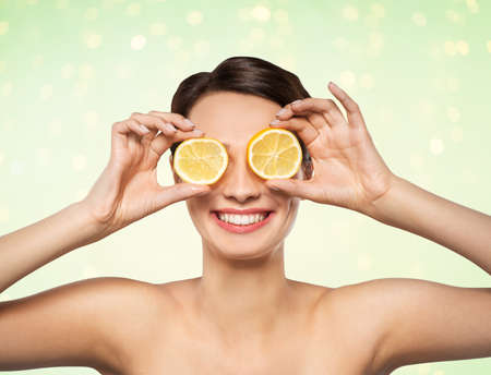 beautiful woman making eye mask of lemon slices