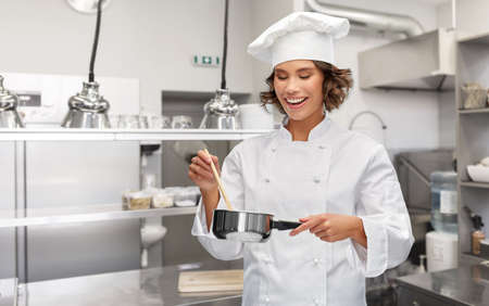 happy smiling female chef with saucepan