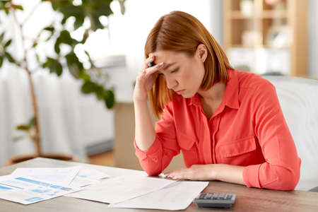 woman with calculator and papers working at home