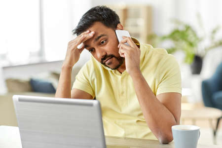 man calling on smartphone at home office