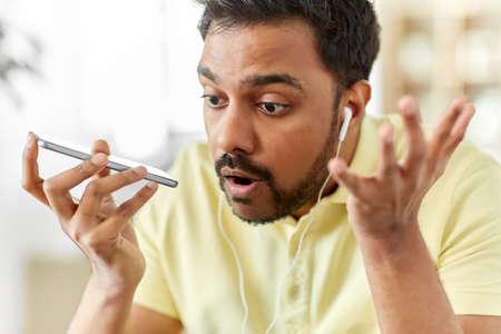 angry man with earphones calling on smartphone