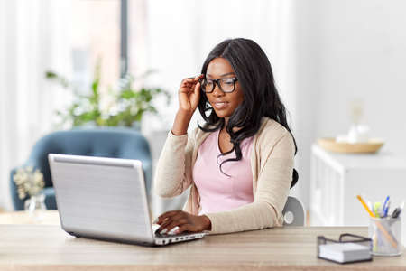 african woman with laptop working at home office
