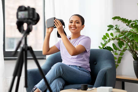 female blogger with camera and vr glasses at home