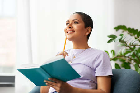 happy african american woman with diary at home