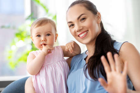 happy mother with little baby daughter at home