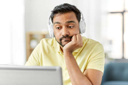 bored man in headphones with laptop works at home