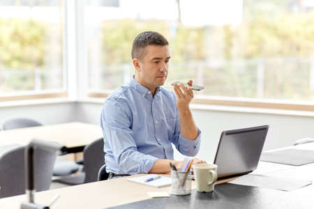 man with smartphone and laptop at home office