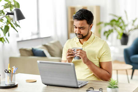 man with laptop drinking coffee at home office