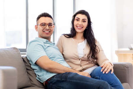 happy couple sitting on sofa at home Imagens
