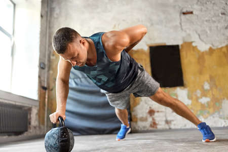 young man doing kettlebell push-ups in gym