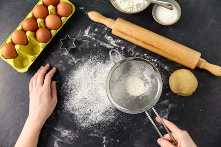 hands with strainer sifting flour on kitchen table