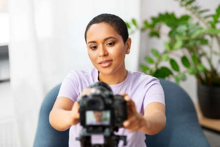 female video blogger adjusting camera at home