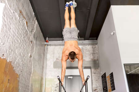 young man exercising on parallel bars in gym
